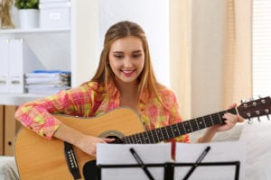 Beautiful smiling woman holding and playing western acoustic guitar portrait. Learning musical instrument music shop or school having fun enjoying hobby concept