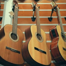 Row of classical acoustic guitars in musical store.