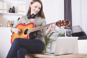 Happy smiling brown haired woman casual dressed playing records on guitar supported by laptop