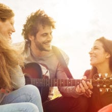Happy group of friends enjoying the summer outdoor playing guitar and singing together