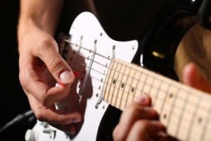 Male hands playing electric guitar with plectrum closeup photo. Learning musical instrument music shop or school blues bar or rock cafe having fun enjoying hobby concept