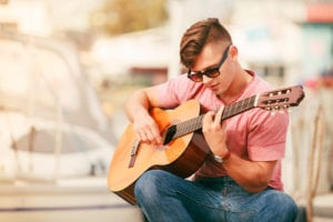 Performance and show time. Young man playing guitar outdoor.