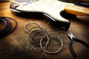 Guitar maintenance. Rolled old guitar strings and an electric guitar. Changing guitar strings.