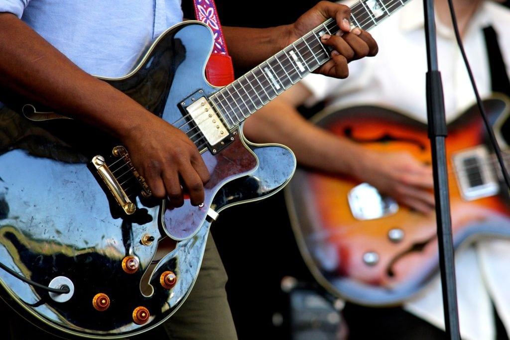 man standing playing guitar